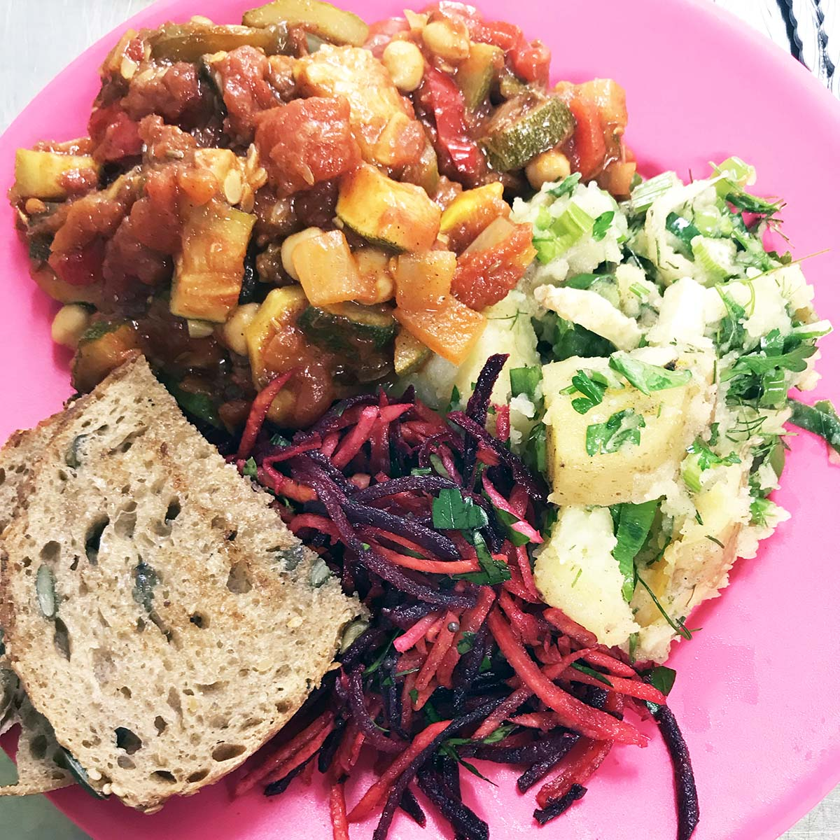 courgette ratatouille with salads and bread on pink plate