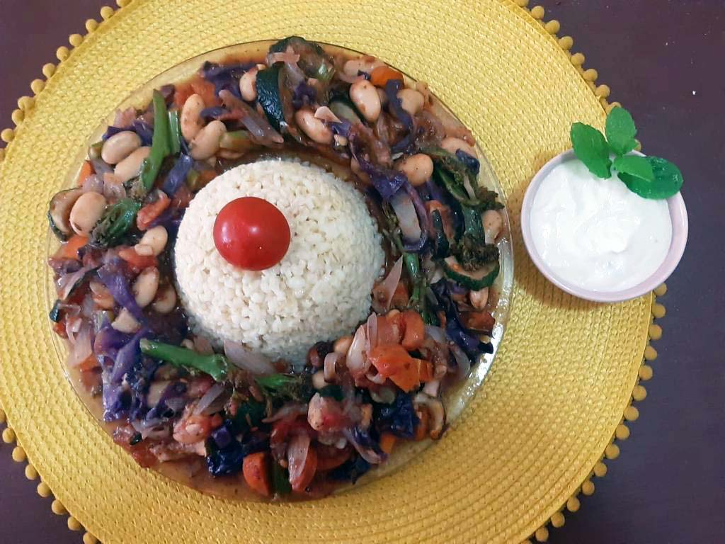 bulgur wheat and vegetables on plate with yoghurt dip