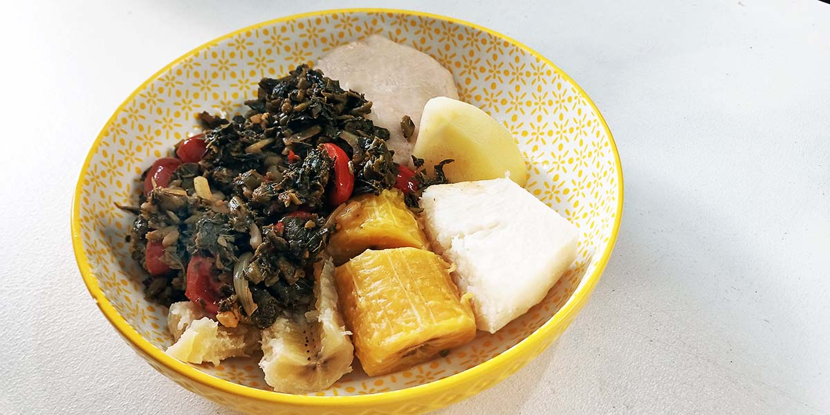 jamaican callaloo and hard food (plantain, green banana, yam, potato, dumplings) on yellow bowl