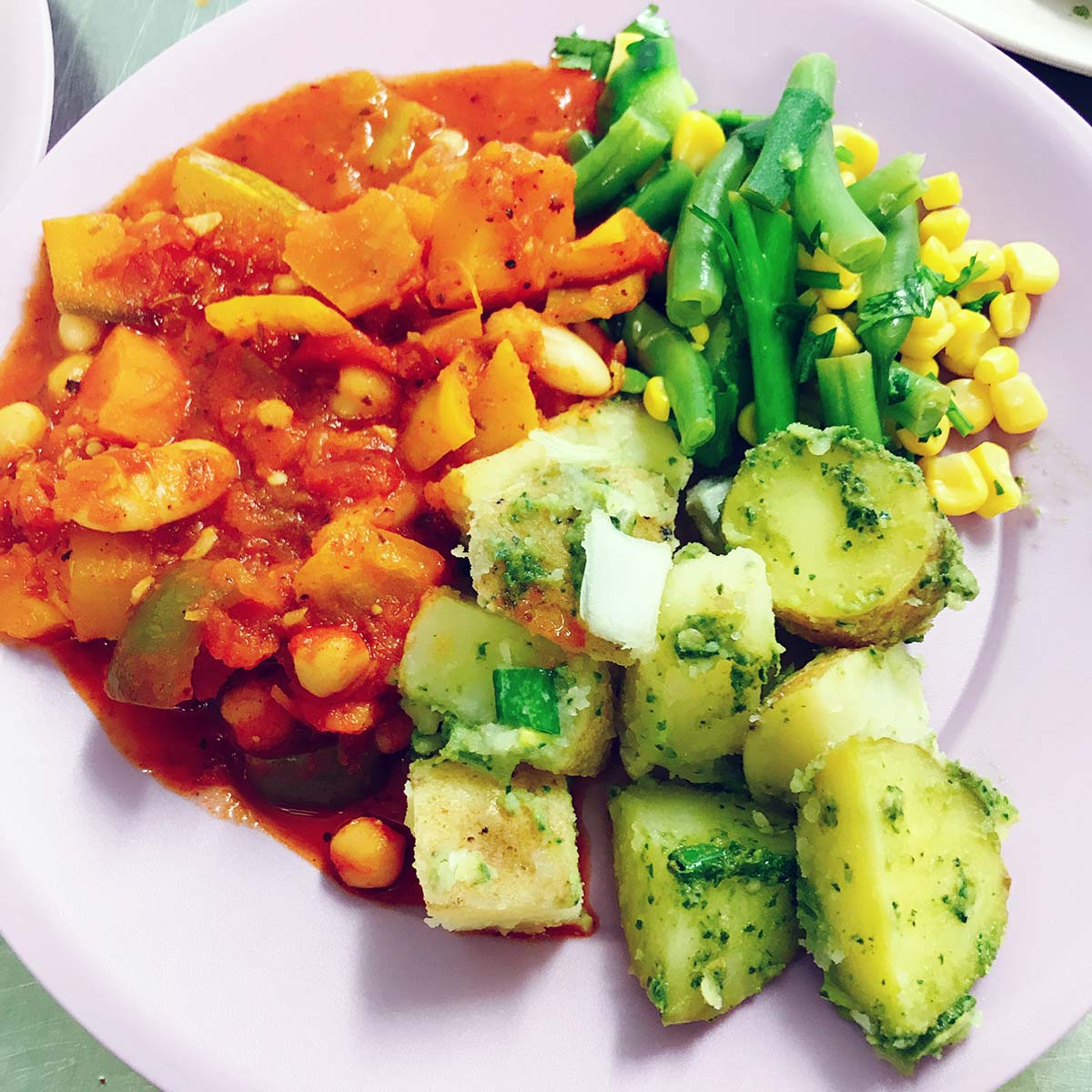 pumpkin stew on lilac plate with potatoes and salad
