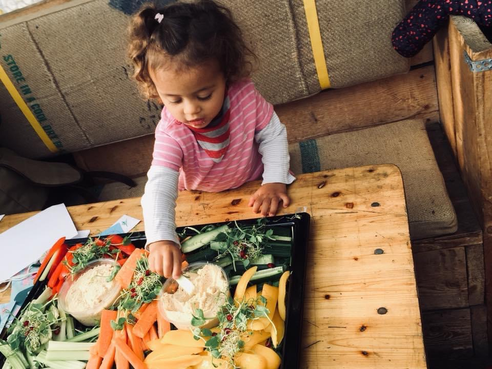 little girl with tray of vegetables and dip