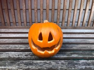 carved pumpkin on wooden bench