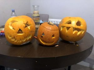 three carved pumpkins on table