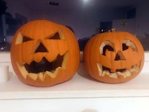 two carved pumpkins on window sill