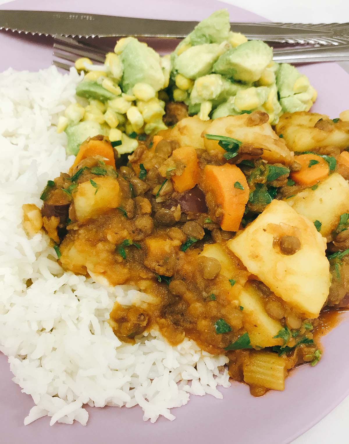 cuban veggie picadillo with rice and avocado salad on purple plate