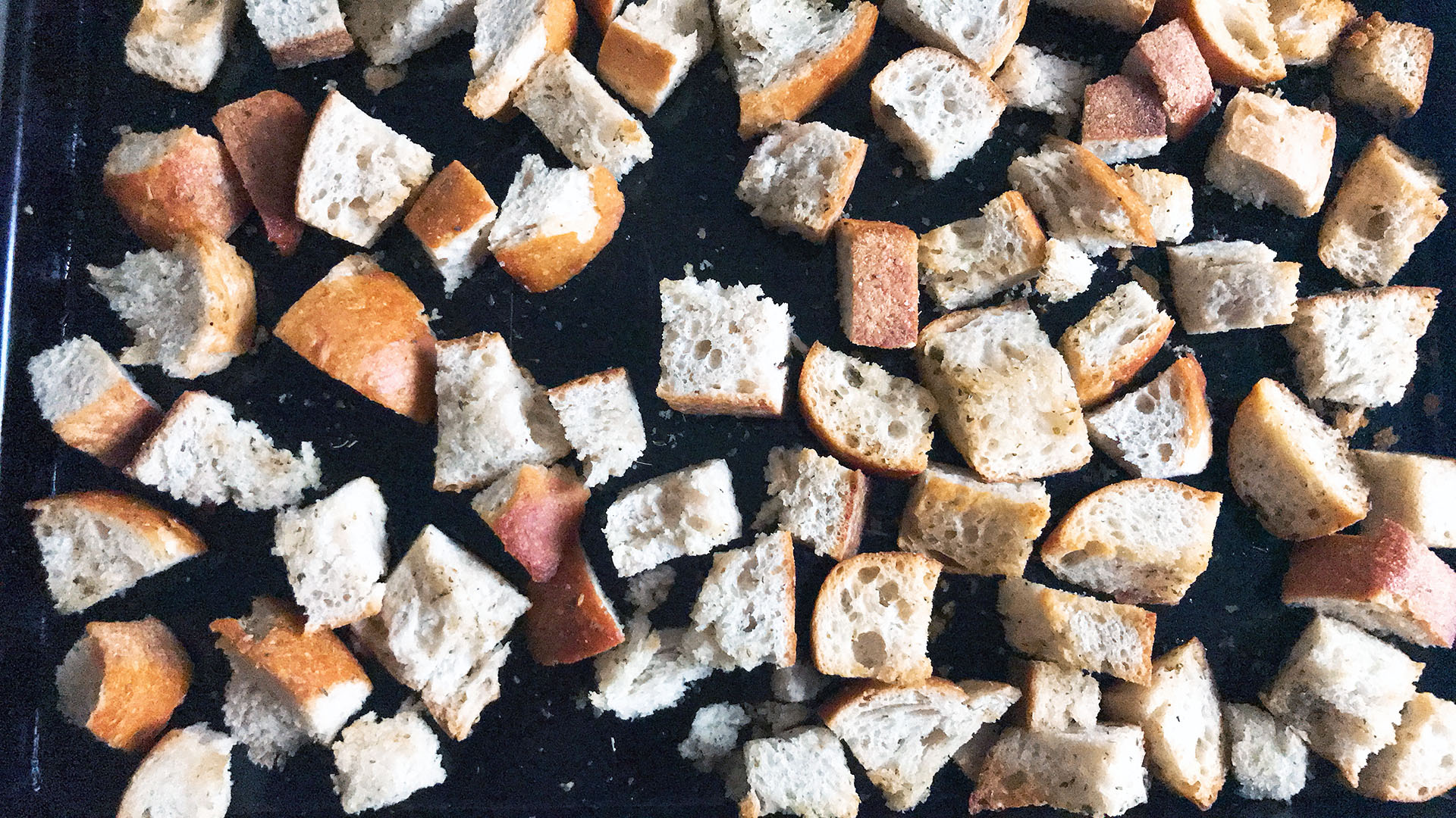 croutons on black baking tray