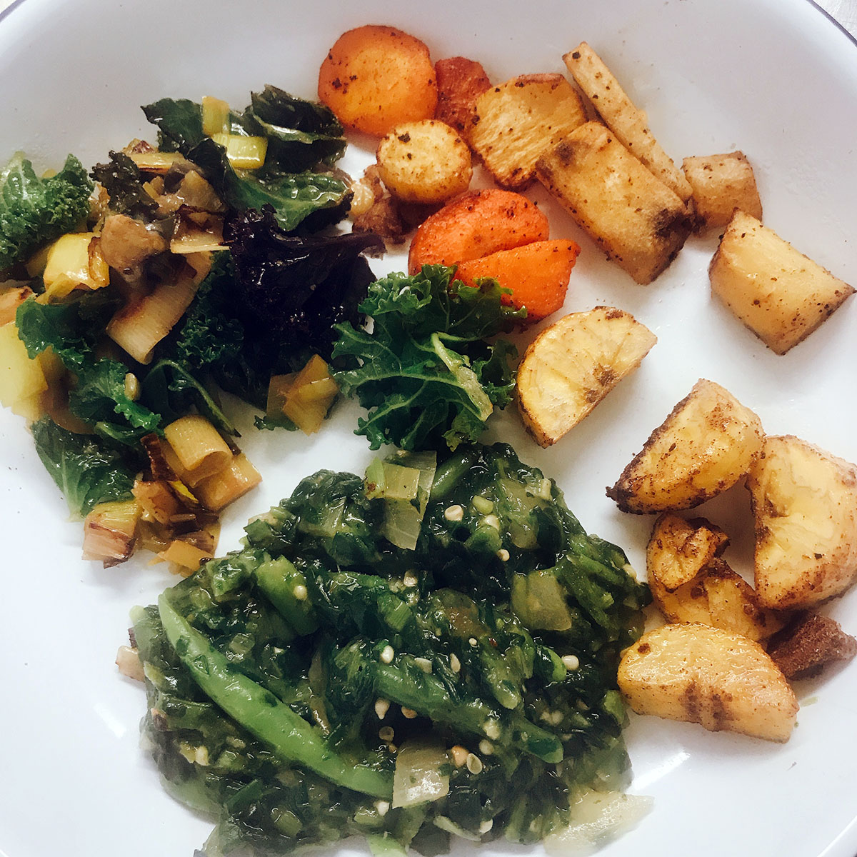 Okra stew on white plate with kale, roasted veg and plantain